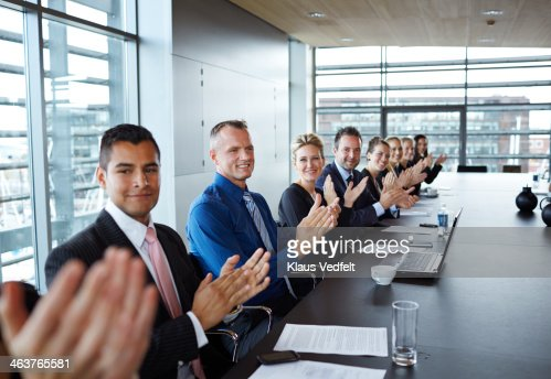 Business people clapping hands at big meeting