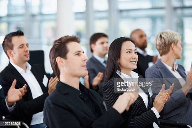 Business people clapping hands during a meeting