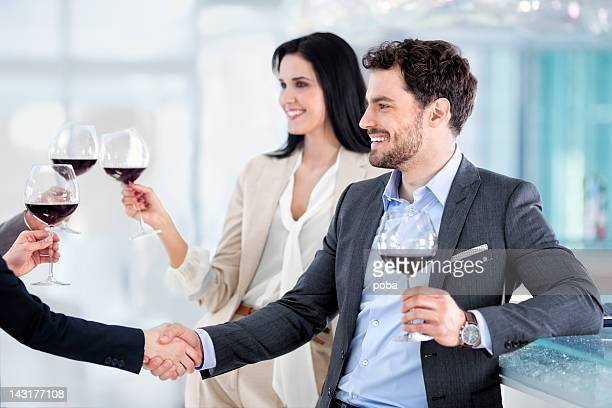 business people,  clinking glasses,shaking hands  congratulating, celebrating  in restaurant