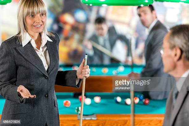 Business people communicating and playing billiard.
