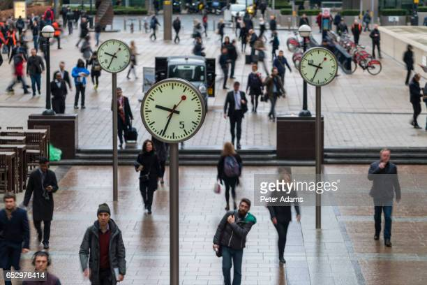 Business people & commuters walking past clocks, Canary Wharf, Docklands of London, UK