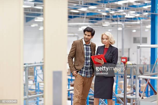 Business people counting stocks in a company warehouse