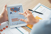 Hand of unrecognizable businessman holding digital tablet with USA map and chart. Hand of his female colleague pointing at map and touching screen. Documents lying nearby on table