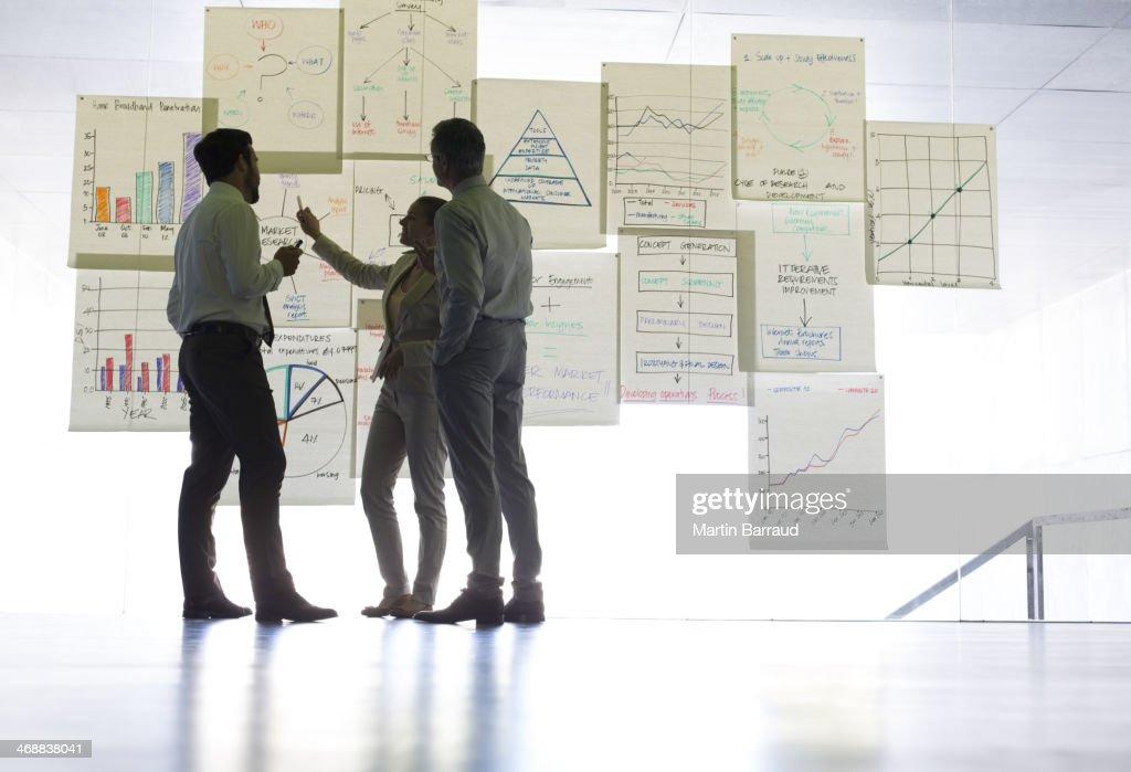 Gens d'affaires discuter de tableaux et graphiques de la suspendre dans le bureau : Photo