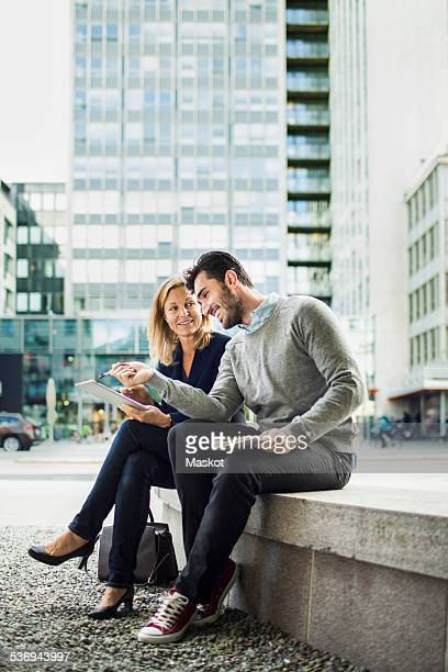 Business people discussing over digital tablet while sitting on seat in city