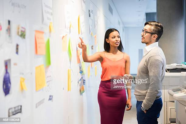 Business people discussing over notes stuck on wall.
