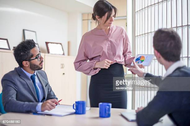 Business people discussing over pie chart at desk