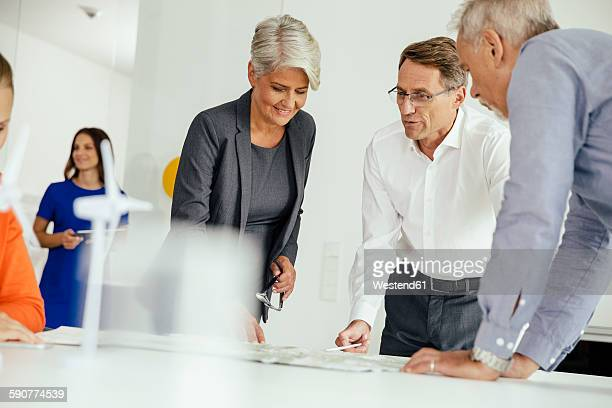 Business people discussing plan with wind turbine model on conference table
