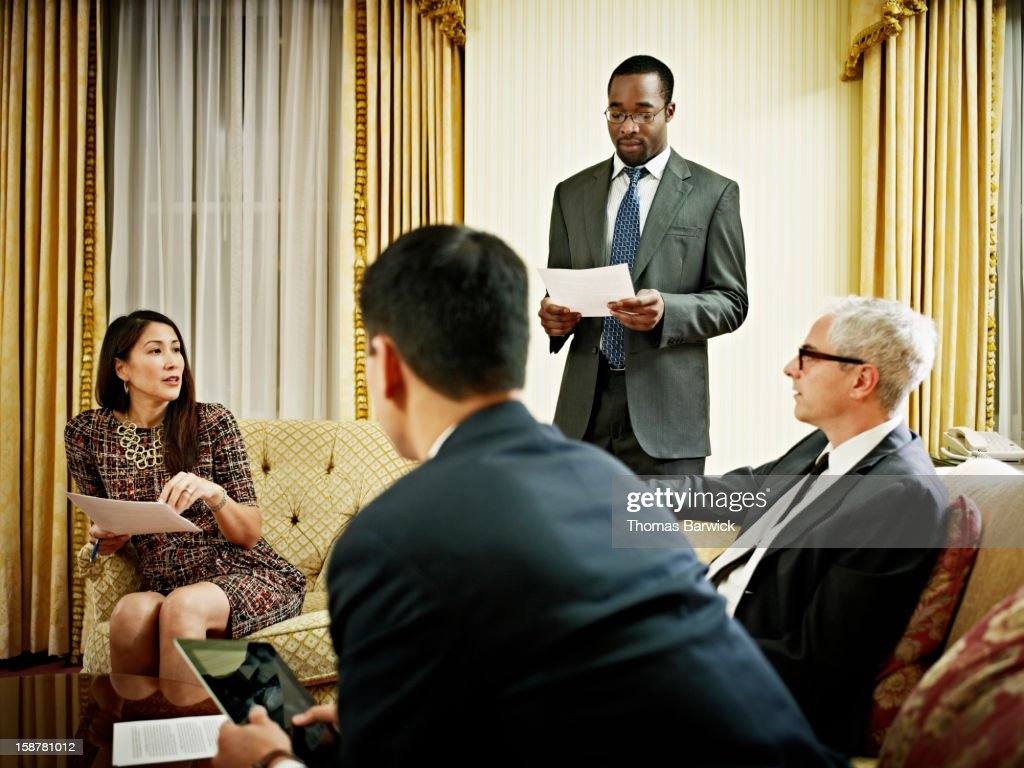 Business people discussing project in hotel room : Stock Photo