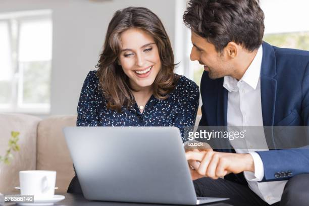 Business people discussing project on laptop at coffee shop