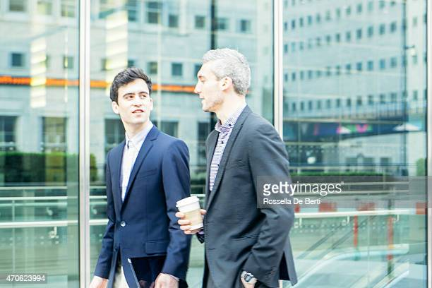 Business People Discussing Project Outdoors, Cityscape On The Background