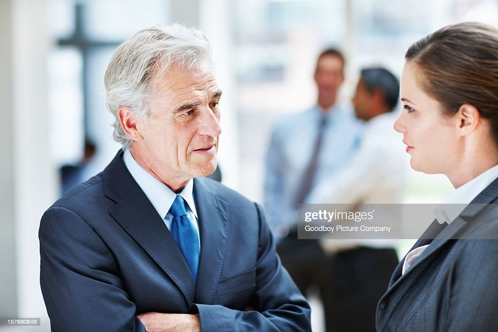 Business people discussing while their blur team in background : Stock Photo