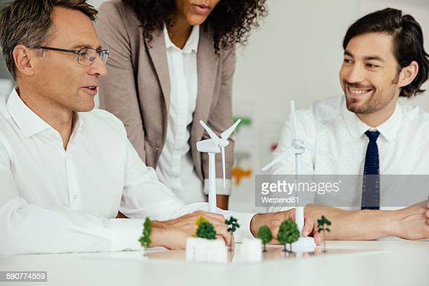 Business people discussing wind turbine model and houses on conference table