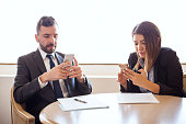 Portrait of a businessman and a businesswoman ignoring each other while using their own smartphones during a meeting