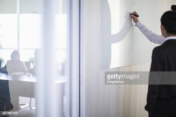 Business people drawing on white board in office