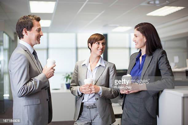 Business people drinking coffee and talking in office