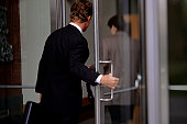 Business people entering office through glass doors, (Rear view)