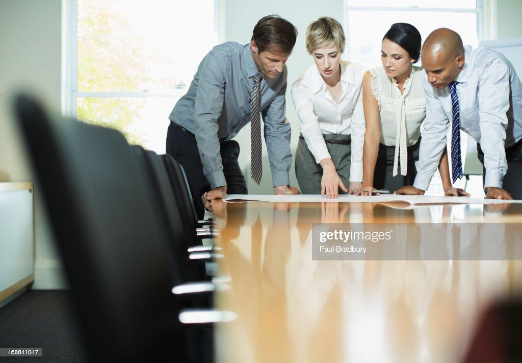 Business people examining blueprints in meeting