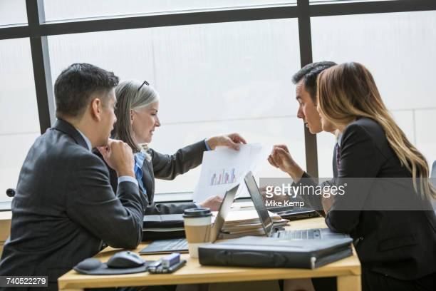 Business people examining chart in meeting
