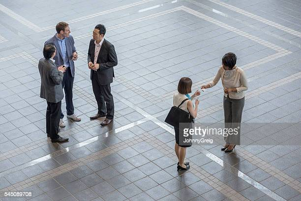 Business people exchange cards and greet , high angle view