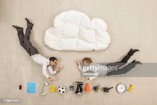 Business people flying between cloud shape pillow and variety of items