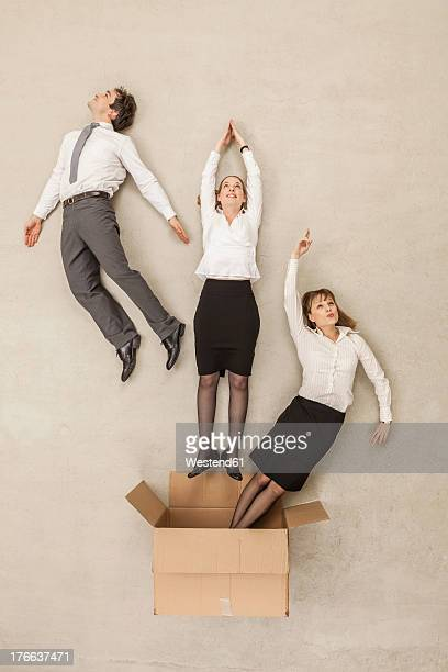 Business people flying out of cardboard box