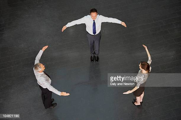 Business people forming circle with outstretched arms