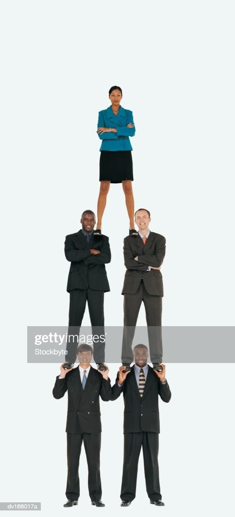 Business people forming human pyramid with businesswoman on top