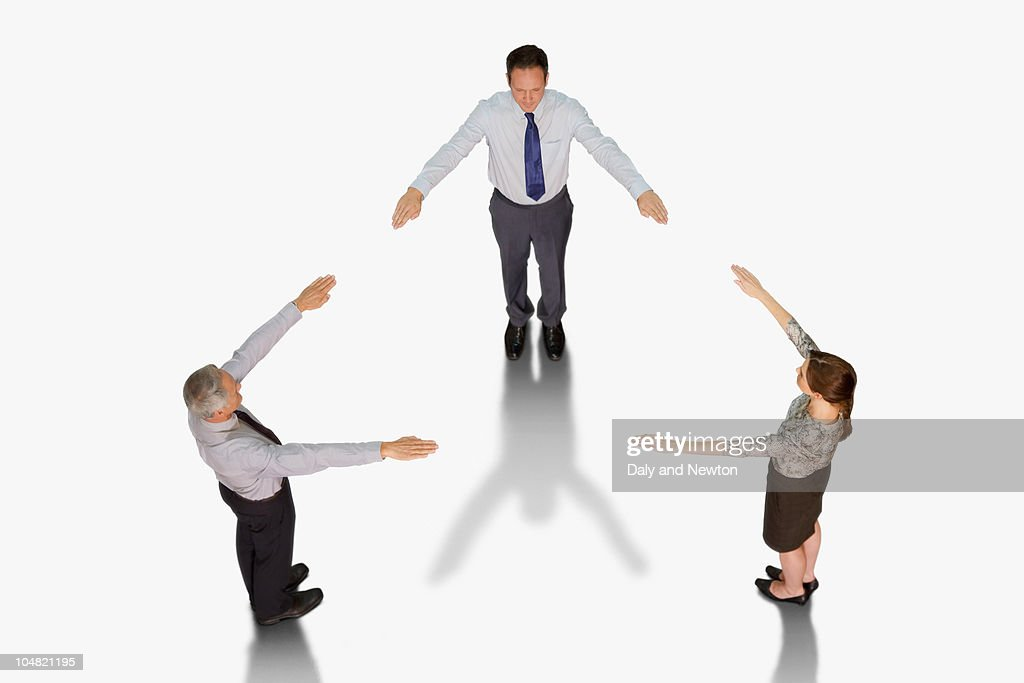 Business people forming triangle with outstretched arms