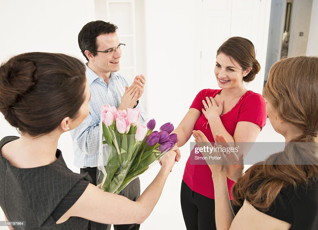 Business people giving colleague flowers : Stock Photo