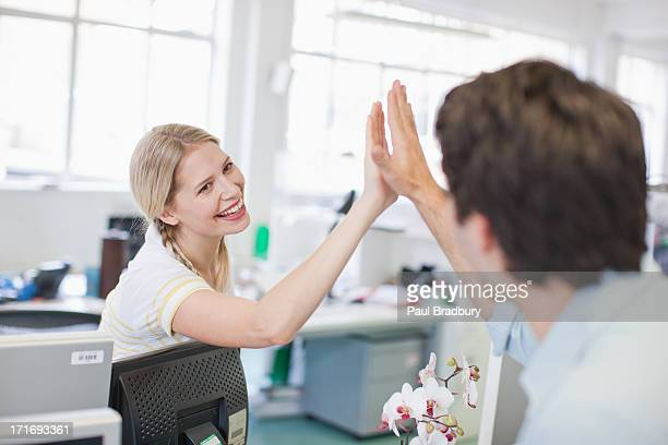 Business people giving high five in office