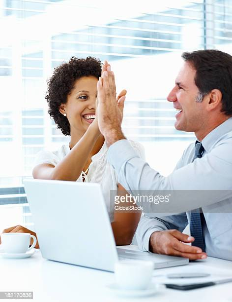 Business people giving high-five to each other at office
