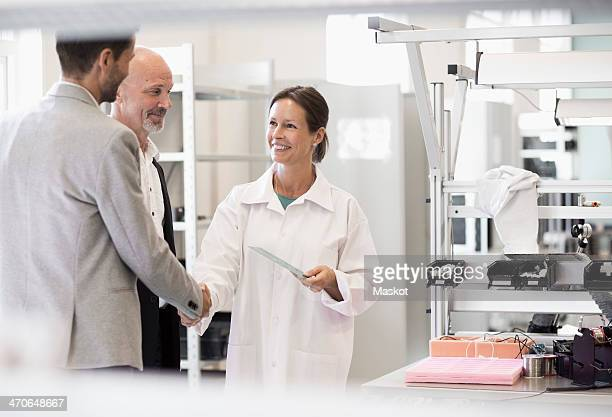 Business people greeting female engineer in manufacturing plant