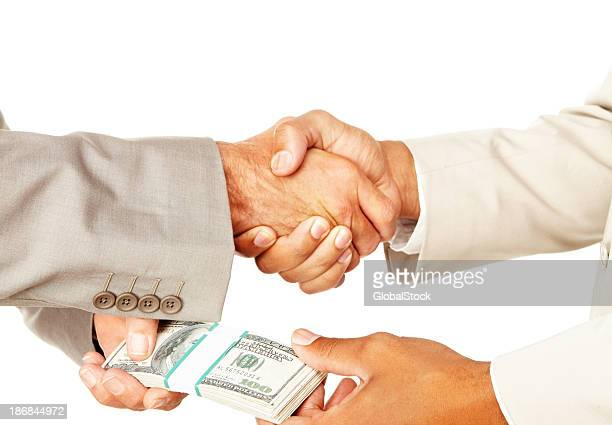 Business people handshake exchanging money