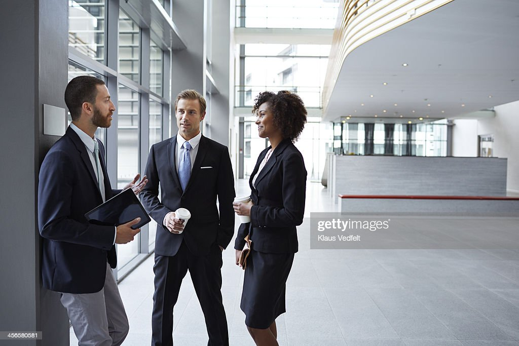 Business people having casual meeting in hall : Stock Photo
