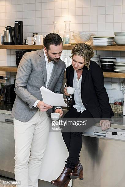 Business people having coffee while reading document at kitchen counter