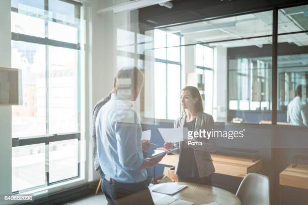 Mensen uit het bedrijfsleven met discussie in glas kantoor