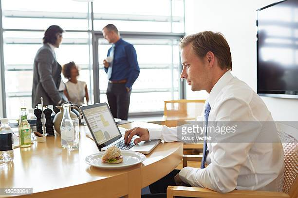 Business people having lunch meeting w. laptop