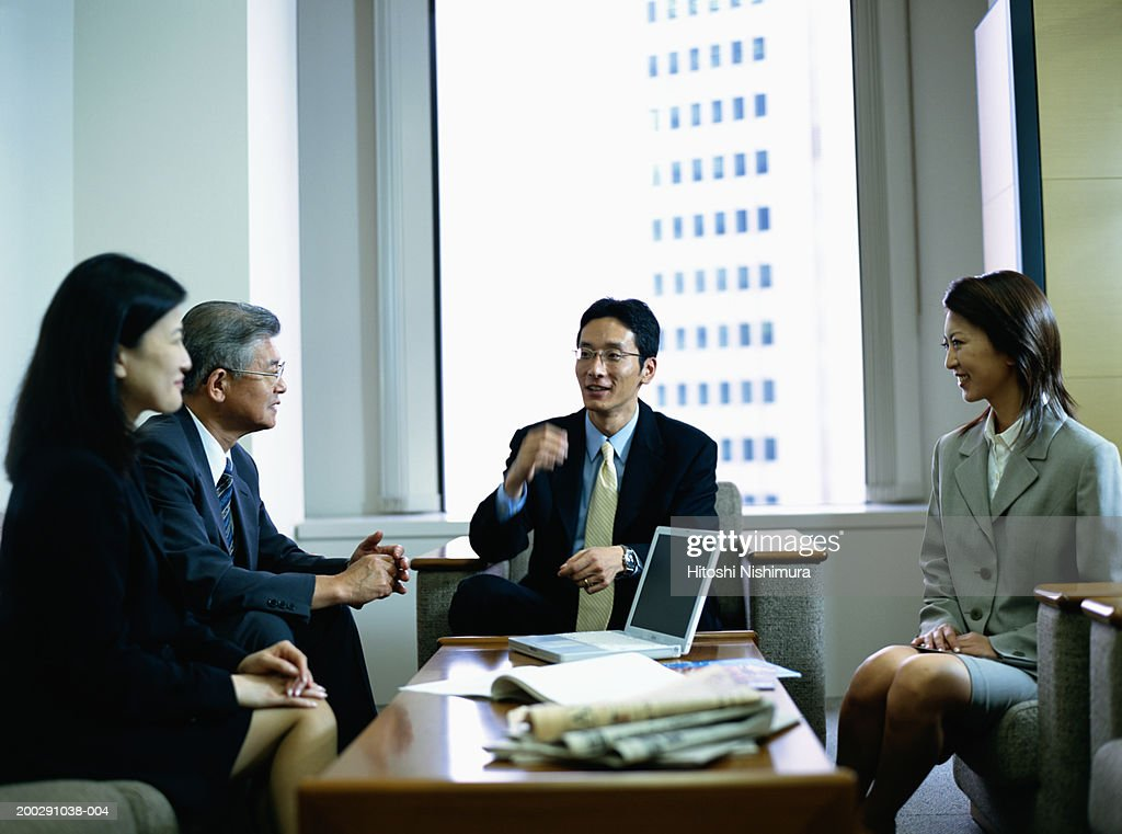 Business people having meeting in office, smiling : Stock Photo