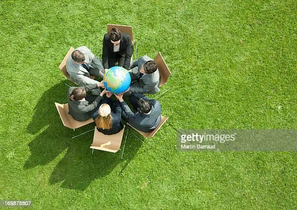 Business people having meeting outdoors looking at globe
