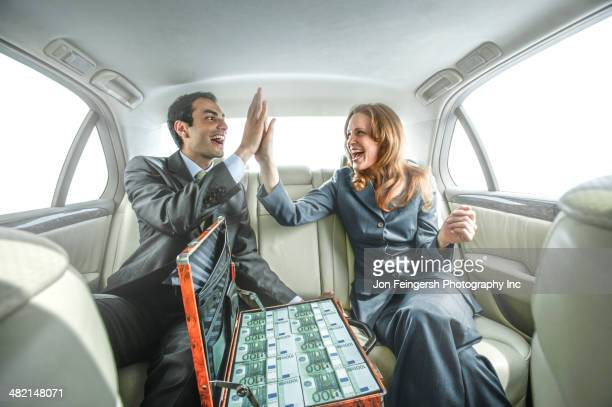 Business people high fiving in backseat of car