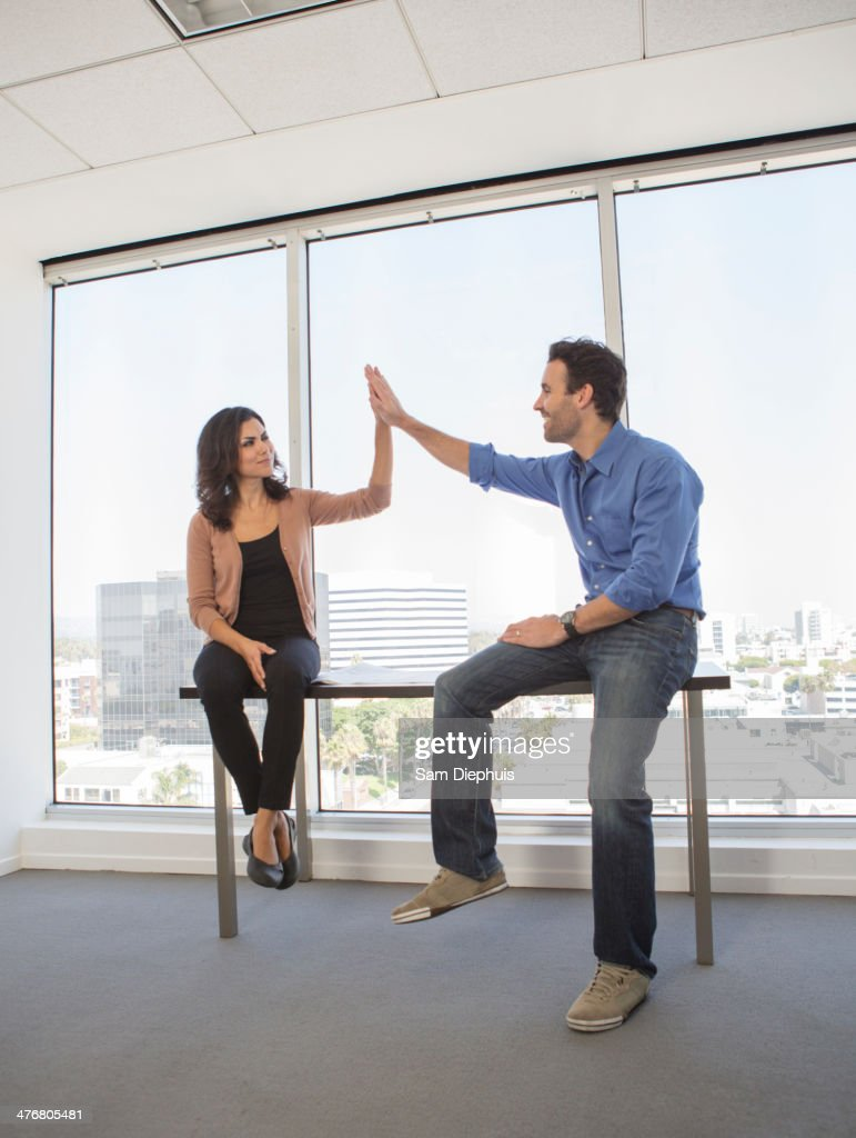 Business people high fiving in office : Stock Photo