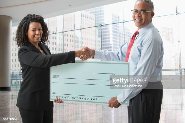Business people holding blank check in office