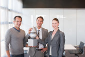 Business people holding cube, sphere and cone