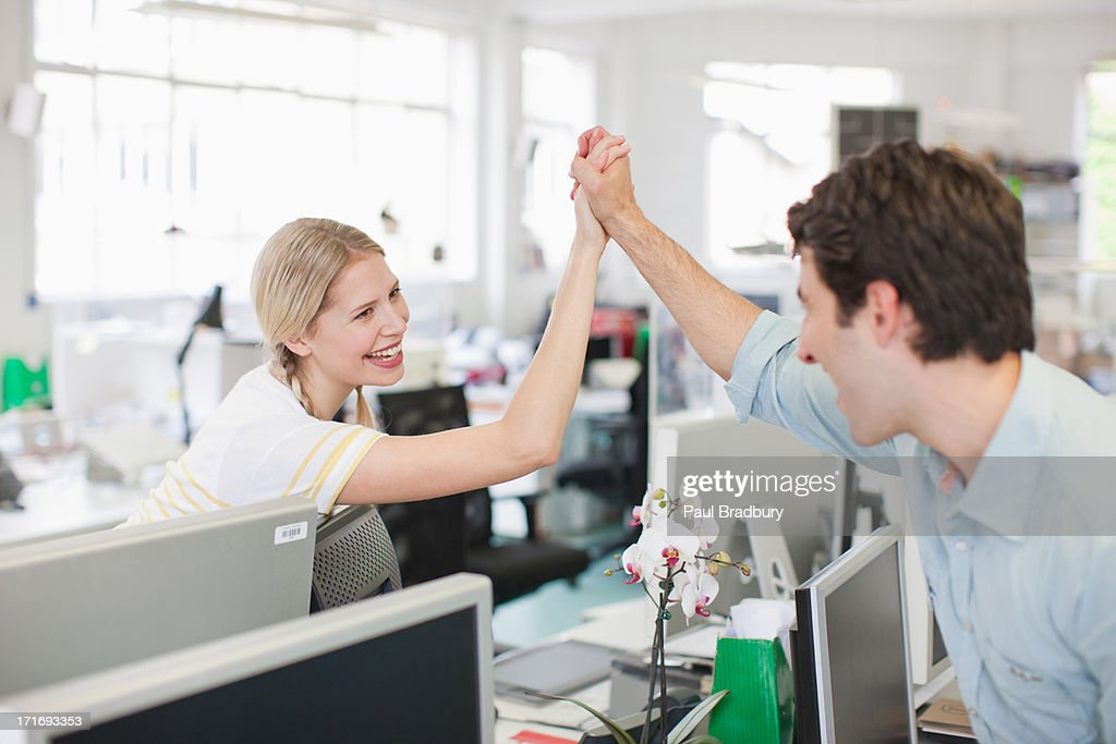 Business people holding hand in office : Stock Photo