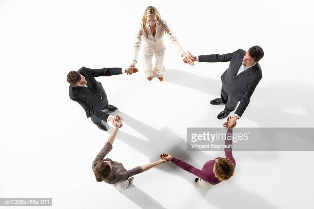 Business people holding hands forming star shape