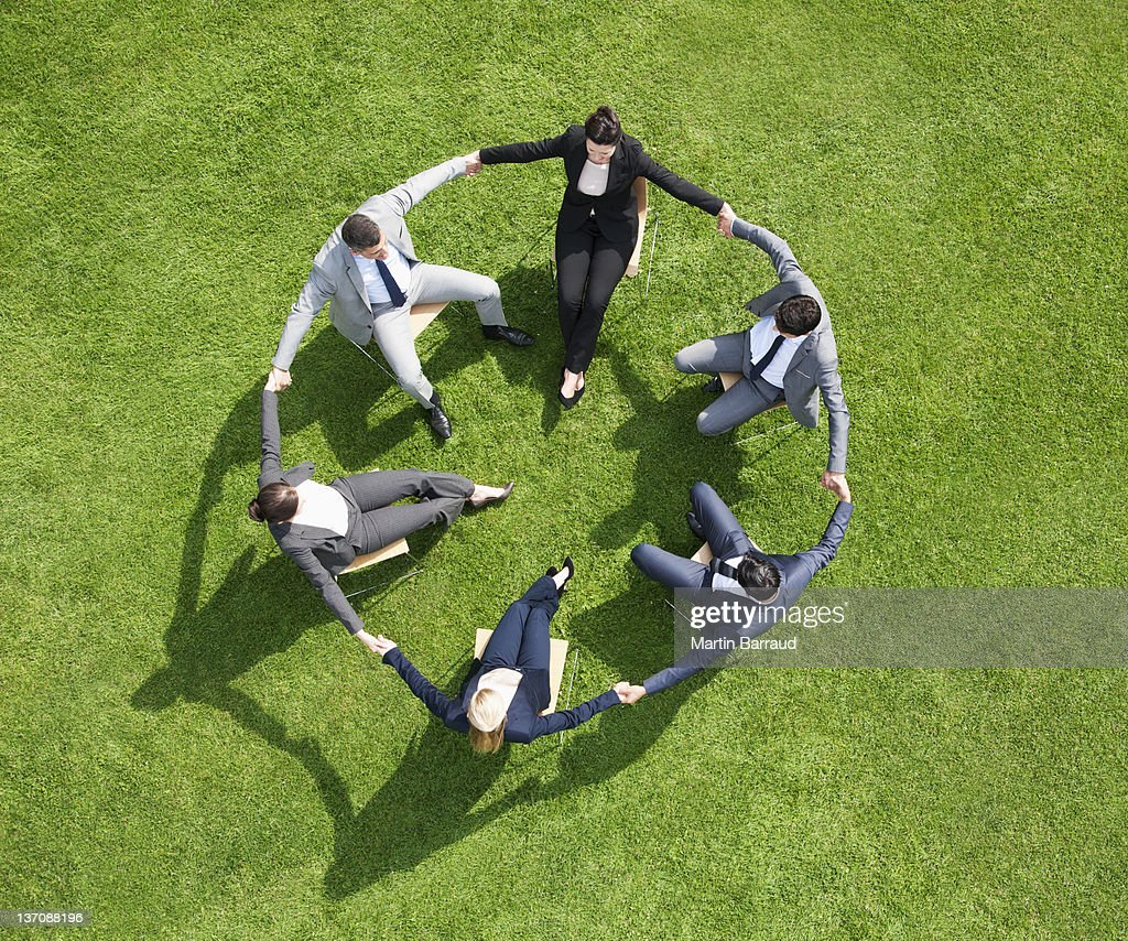 Business people holding hands in circle outdoors : Stock Photo