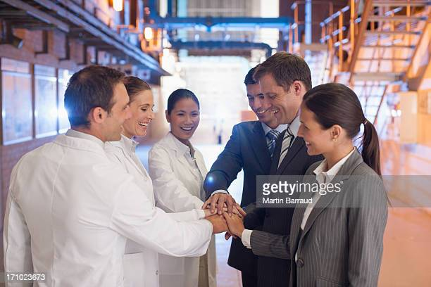 Business people holding hands with scientists in factory
