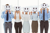 Business people holding happy smileys in front of their faces in office
