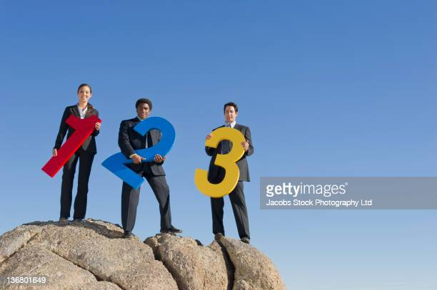 Business people holding large numbers on rock